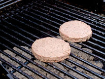 Raw burgers on the BBQ Stock Image
