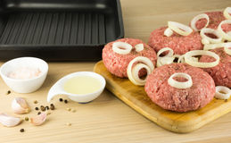 Raw burgers, beef on a cooting board, frying pan on woogen backg Stock Photography