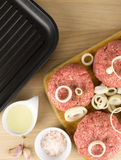 Raw burgers, beef on a cooting board, frying pan on woogen backg Royalty Free Stock Photo