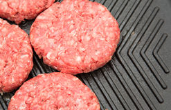 Raw burgers on a griddle Stock Photography