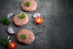 Raw burgers and ingredients. Raw beef and pork burgers and ingredients for cooking at slate background Stock Images