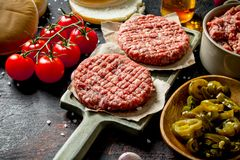 Raw burgers with jalapeno chillies, tomatoes and scones royalty free stock photos