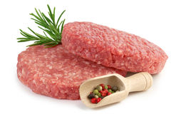 Raw burgers, rosemary and pepper Royalty Free Stock Images