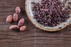 Raw Cacao Nibs and cacao beans over rustic wooden background. Raw Cacao Nibs in a ceramic plate and cacao beans over rustic wooden background. Top view stock photography
