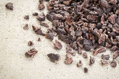 Raw cacao nibs. Close-up of a pile of raw cacao nibs on a rough white painted barn wood background royalty free stock image