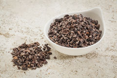 Raw cacao nibs. Small ceramic bowl of raw cacao nibs against a ceramic tile background with a copy space royalty free stock photo