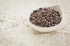 Raw cacao nibs. Small ceramic bowl of raw cacao nibs against a ceramic tile background with a copy space royalty free stock photography