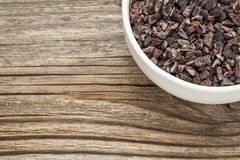 Raw cacao nibs. In a small ceramic bowl against grained wooden background royalty free stock photos