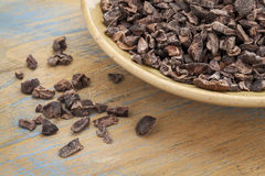 Raw cacao nibs. In a small ceramic bowl against grunge wooden background stock photos