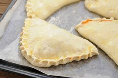 Raw calzone pizzas on papered frying pan Royalty Free Stock Photography