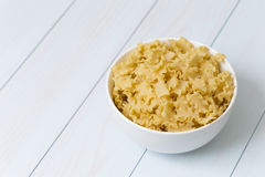 Raw campanelle pasta in a white bowl. On blue wood table Stock Photography