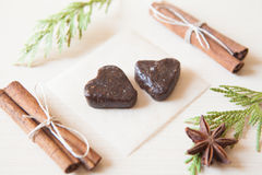 Raw candies. Heart-shaped raw candies made of date fruit,nuts decorated with cinnamon sticks,cardamom,thuja branches on light wooden background indoors.Healthy Stock Images