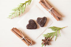 Raw candies. Heart-shaped raw candies made of date fruit,nuts decorated with cinnamon sticks,cardamom,thuja branches on light wooden background indoors.Healthy Stock Photo