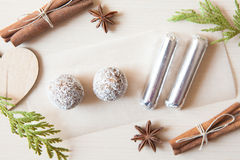 Raw candies. Made of date fruit,nuts,cocoa,coconut decorated with cinnamon sticks,cardamom,thuja branches on light wooden background indoors.Healthy and raw Stock Photo