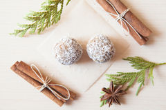 Raw candies. Made of date fruit,nuts,cocoa,coconut decorated with cinnamon sticks,cardamom,thuja branches on light wooden background indoors.Healthy and raw Stock Photography
