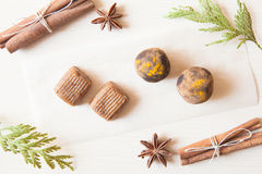Raw candies. Made of date fruit,nuts,curry,cocoa decorated with cinnamon sticks,cardamom,thuja branches on light wooden background indoors.Healthy and raw sweet Stock Images