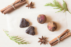 Raw candies. Made of date fruit,nuts, hibiscus,cocoa decorated with cinnamon sticks,cardamom,thuja branches on light wooden background indoors.Healthy and raw Royalty Free Stock Image