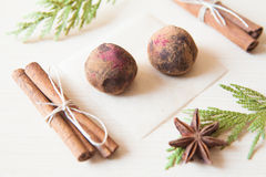 Raw candies. Made of date fruit,nuts, hibiscus,cocoa decorated with cinnamon sticks,cardamom,thuja branches on light wooden background indoors.Healthy and raw Royalty Free Stock Photography