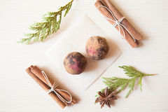 Raw candies. Made of date fruit,nuts, hibiscus,cocoa decorated with cinnamon sticks,cardamom,thuja branches on light wooden background indoors.Healthy and raw Royalty Free Stock Photo