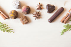 Raw candies. Made of date fruit,nuts, hibiscus,curry,cocoa,coconut decorated with cinnamon sticks,cardamom,thuja branches on light wooden background indoors Royalty Free Stock Images