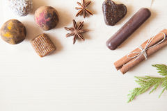 Raw candies. Made of date fruit,nuts, hibiscus,curry,cocoa,coconut decorated with cinnamon sticks,cardamom,thuja branches on light wooden background indoors Royalty Free Stock Image