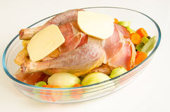 Baking guinea fowl. Raw carcase of guinea fowl in pan with spices, butter, Black forest ham and vegetables - prepared for baking Royalty Free Stock Photo
