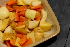 Raw carrot, onion and potato in a ceramic dish prepared for roasting Stock Photo