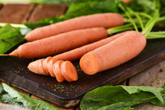 Raw carrots on a chopping board Stock Image