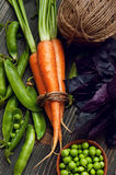 Raw carrots, green peas and basil on wooden table Stock Photography
