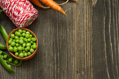 Raw carrots, green peas and red twine on wooden table Royalty Free Stock Photos