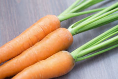 Raw carrots with green tops. On wooden background Stock Photo