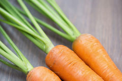 Raw carrots with green tops. On wooden background Royalty Free Stock Photography