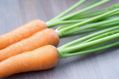 Raw carrots with green tops. On wooden background Stock Images