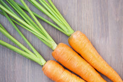 Raw carrots with green tops. On wooden background Royalty Free Stock Image