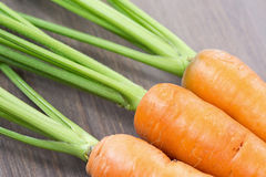 Raw carrots with green tops. On wooden background Stock Image