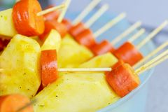 Raw carrots and potatoes, strung on a skewer for grilling. Prepa. Red for a picnic. Concept of healthy, useful food. Selective focus. Close-up Stock Photography