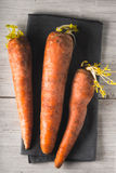 Raw carrots on the white wooden background vertical. Raw carrots on the white wooden scratched background top view vertical Stock Images