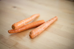Raw carrots on wood table Royalty Free Stock Images