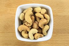 Raw Cashew Nuts in a Bowl. Overhead shot of raw cashew nuts in a white bowl on a wooden board background. Cashew nuts are the seeds of the cashew tree stock image