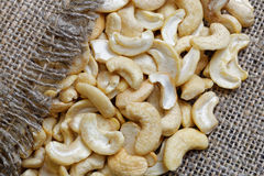 Raw cashew nuts lie on sacking Stock Images