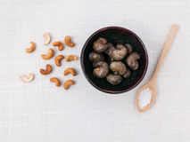 Raw cashews nut in the bowl with salt. Royalty Free Stock Image