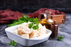 Raw cauliflower. In bowl and on a table Stock Photo
