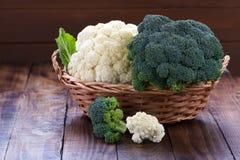 Raw cauliflower and broccoli. In wicker basket on rustic background Stock Photo