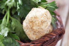 Raw celery root. Fresh raw celery root with green leaves in woven basket Stock Images