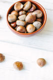 Raw chestnuts in ceramic bowl. Raw chestnuts in ceramic bowl on white surface Royalty Free Stock Photos