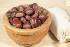 Raw chestnuts beside sacks of chestnut flour Stock Photography