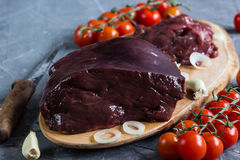 Raw chicken and beef liver. On board on stone table. Selective focus Stock Images
