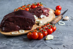 Raw chicken and beef liver. On board on stone table. Selective focus Stock Photo