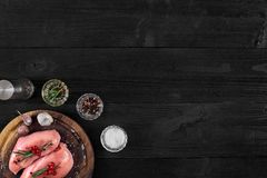 Raw chicken breast and condiments in a rustic wooden setting, top view. Still life. Copy space. Flat lay Stock Photos