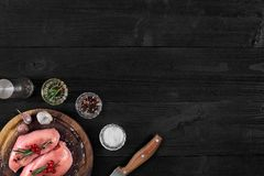 Raw chicken breast and condiments in a rustic wooden setting, top view. Still life. Copy space. Flat lay Royalty Free Stock Photos